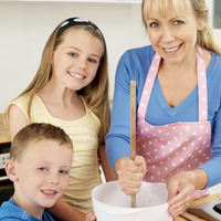 Woman using wooden ladle, boy and girl smiling at the camera