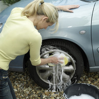 Woman washing car wheel