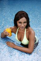 Woman with a glass of orange juice leaning on pool edge
