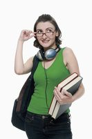 Woman with backpack and books adjusting her glasses