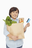 Woman with groceries holding up a credit card