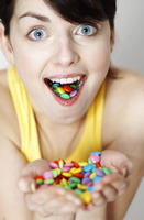 Woman with handful and mouthful of candies