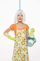 Woman with mop on her head carrying a pail of cleaning products