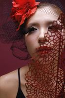 Woman with net and flower decorating her hair holding red leaf over face