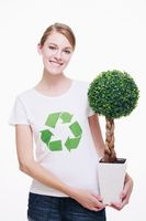 Woman with recycling symbol on her t-shirt holding a potted plant