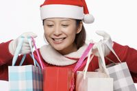 Woman with santa hat carrying shopping bags