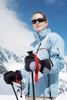 Woman with sunglasses holding on skiing poles