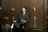 Woman worshipping a businessman who is sitting on the shelf meditating