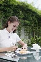 Woman writing in organizer while having breakfast outdoors