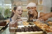 Women choosing cakes and tarts from display case