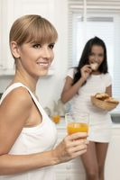 Women eating and drinking in the kitchen