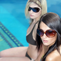Women in bikini and trendy sunglasses sitting by the poolside