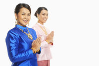 Women in traditional clothing showing greeting gesture