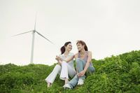Women relaxing outdoors with wind mill in the background