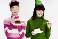 Women with party hat eating cake