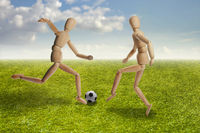 Wooden dummies models playing soccer