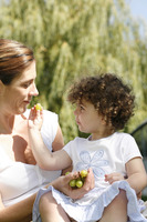 Young girl feeding her mother some green grapes