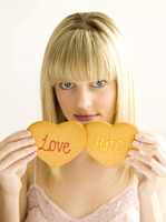 Young teen holding two cookies, love and hate
