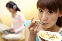 Young woman enjoying her food, another woman listening to music and using laptop