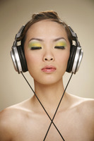 Young woman listening to music on the headphones