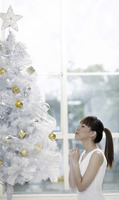 Young woman wishing upon a christmas tree