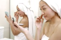Young women applying make-up