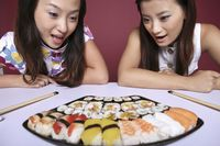Young women looking at the variant of sushi with their mouths opened