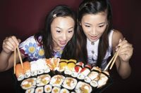 Young women looking at the variant of sushi