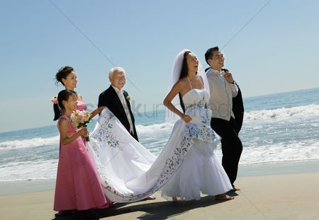 Wedding : Bride and groom walking with family on beach
