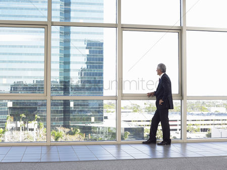 Interior : Businessman looking out of office window