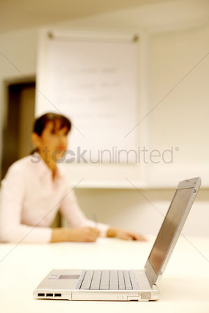 Environment : Businesswoman writing on the background with the focus on a laptop