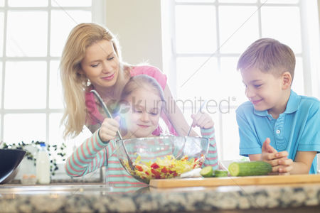 Girl : Family looking at girl mixing salad in kitchen