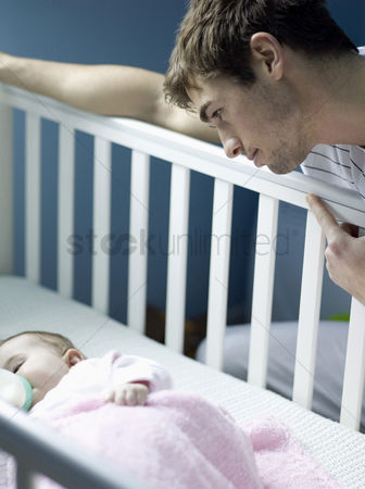 Cute : Father watching baby girl sleeping in the crib