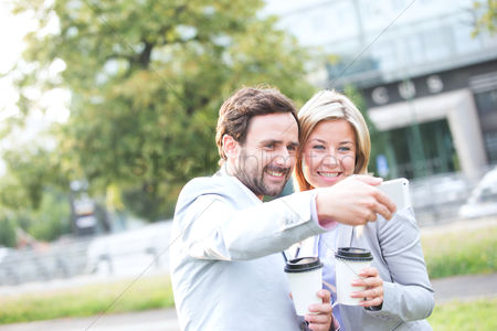 Selfie : Happy business couple taking selfie while holding disposable cups in city