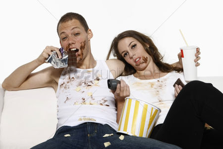 Food : Man and woman eating while watching television on couch