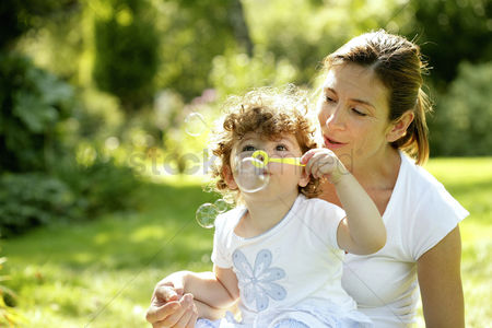 Girl : Mother and daughter playing with soap bubbles