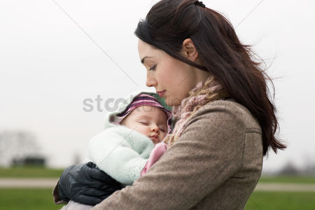 Girl : Mother carrying sleeping baby