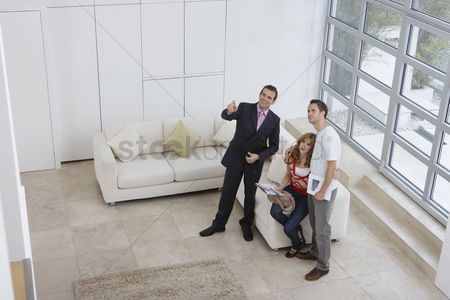 Interior : Real estate agent showing couple new home elevated view