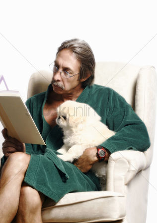 Cute : Senior man hugging his dog while reading book on the couch