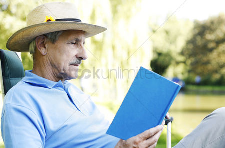 Park Outdoor : Senior man sitting on a chair reading book
