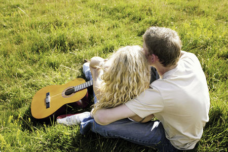 Romantic : Top angle view of a couple sitting on the grass hugging