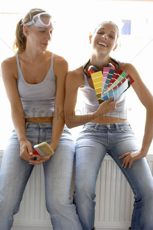 Interior : Two women in jeans sitting together with one holding a brush while the other holding colour cards