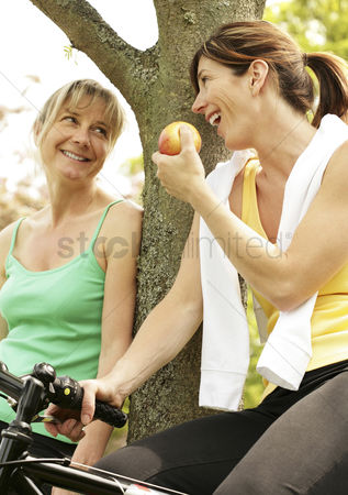 Park Outdoor : Two women talking while sitting on bicycles