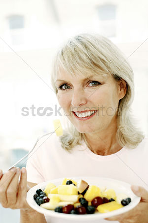Food : Woman holding a bowl of fruits