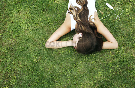 Environment : Woman lying forward on the grass listening to music