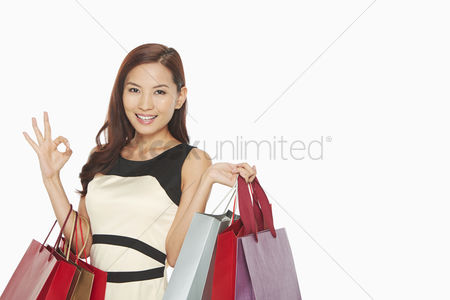 Shopping : Woman with shopping bags showing hand gesture