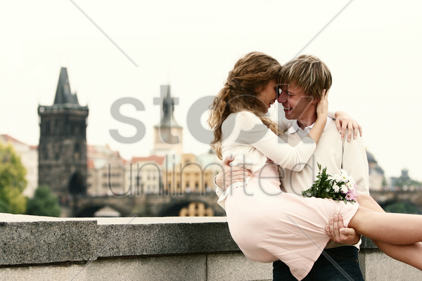 a guy carrying his girlfriend on his arms stock photo