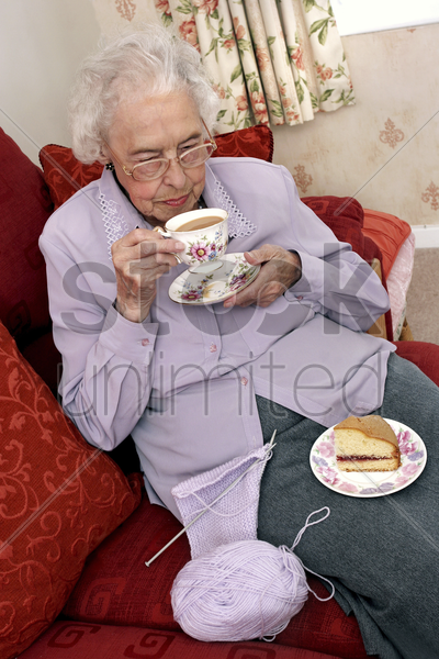 an old bespectacled woman stop knitting for her tea time stock photo