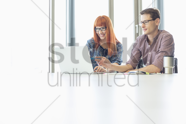 business colleagues using laptop at desk in creative office stock photo