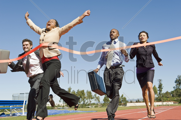 business people crossing the winning line stock photo